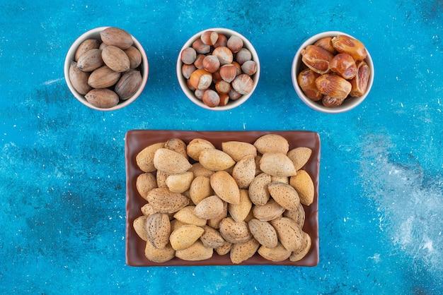 Geschälte nüsse in einem teller und schalen auf der blauen oberfläche