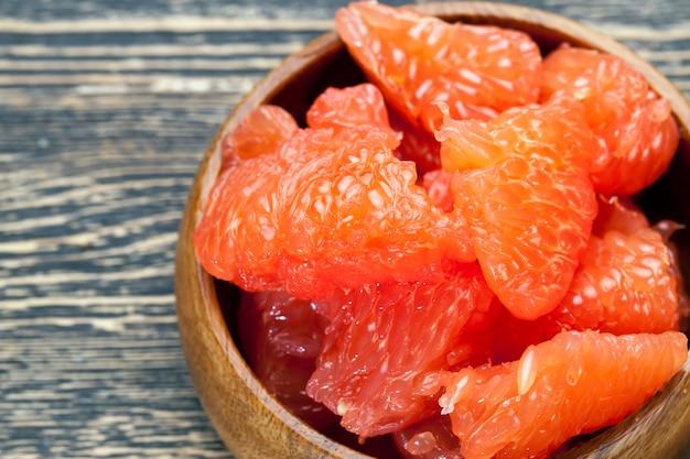 Geschälte rote grapefruit beim kochen in scheiben geteilt, saftige zitrus-grapefruit