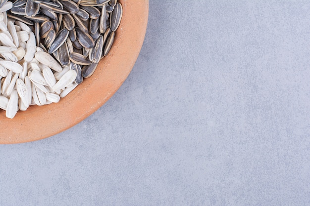 Geschälte sonnenblumenkerne auf teller auf marmor.