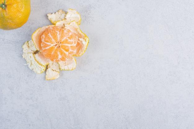Geschälte und ganze mandarine auf grauem hintergrund.