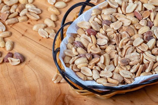 Geschälte und geröstete erdnüsse in einem kleinen körbchen