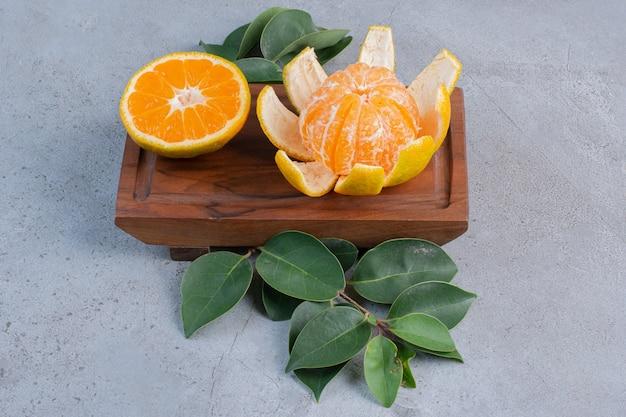 Geschälte und geschnittene mandarinen auf einem kleinen brett auf marmorhintergrund.