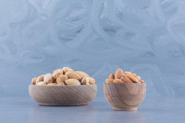 Geschälte und ungeschälte mandeln auf dem marmorhintergrund.