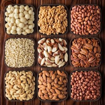 Geschälte verschiedene nüsse auf holztisch. rohkost als snack mischen.