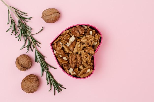 Geschälte walnüsse in geschenkbox in herzform mit ungeschälten und rosmarin auf rosa hintergrund. nützliches nahrhaftes proteinprodukt. konzept zum feiertag. ansicht von oben.