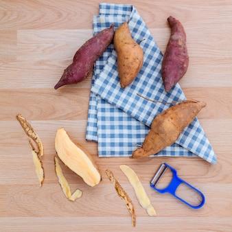Geschälte zwei vielzahl der süßkartoffeln mit schäler auf rustikaler hölzerner tabelle.
