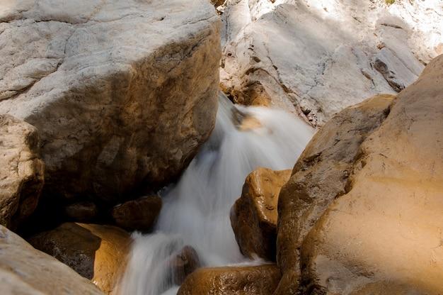 Geschäumtes wasser, das zwischen steinen in der schlucht läuft