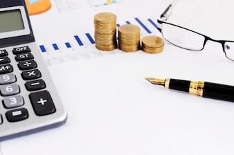 Geschäfts-Finanzkonzept mit Abschluss oben des Füllfederhalters und des Münzenstapels
