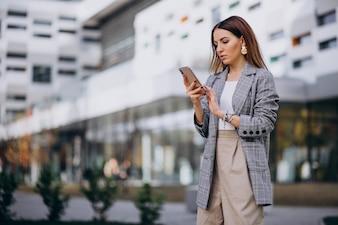 Geschäftsfrau, die draußen Telefon in der Straße durch das Gebäude verwendet