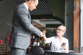 Geschäftsfrau, die Hände mit ihrem Partner in cafà © rüttelt