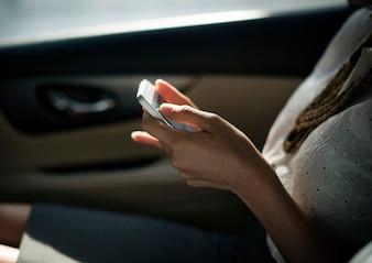 Geschäftsfrau, die Handy am Rücksitz des Autos verwendet