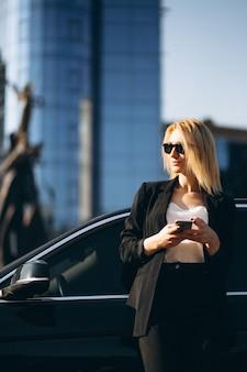 Geschäftsfrau durch das Auto in der Stadt unter Verwendung des Telefons