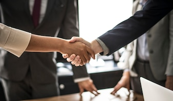Geschäftsleute, die Hände in einem Konferenzzimmer rütteln