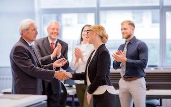 Geschäftsleute, die Hände nach erfolgreichen Verhandlungen im Büro rütteln