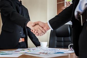 Geschäftsleute, die Hände schütteln, eine Sitzung beenden