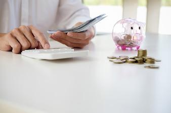 Geschäftsleute, die Münzen und Sparschwein am Schreibtisch schützen. speicherndes Konzept