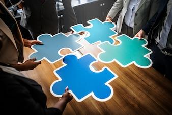 Geschäftsleute, die Puzzlespielstücke anschließen
