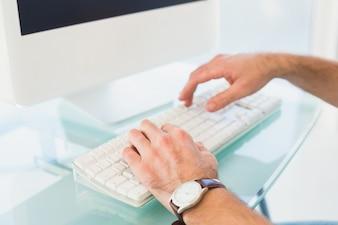 Geschäftsmann, der auf Computertastatur in seinem Büro schreibt