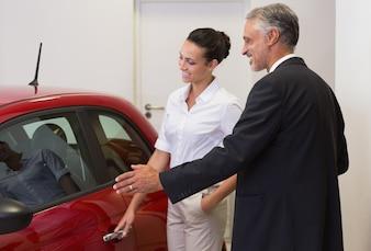 Geschäftsmann, der einer Frau ein Auto zeigt