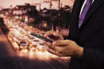 Geschäftsmann, der seine Handy-Nachtlichtstraße verwendet