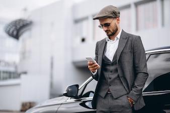 Geschäftsmann durch das Auto, das am Telefon spricht