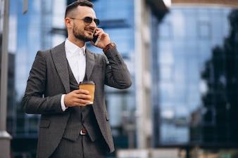 Geschäftsmann mit trinkendem Kaffee des Telefons äußerem Wolkenkratzer