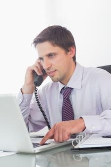 Geschäftsmann unter Verwendung des Telefons und des Laptops am Schreibtisch