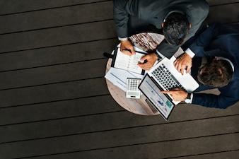 Geschäftsmänner, die draußen Café-Konzept bearbeiten