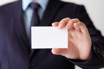 Geschäftsmannhand, die leere weiße Visitenkarte mit Kopienraum für Text hält