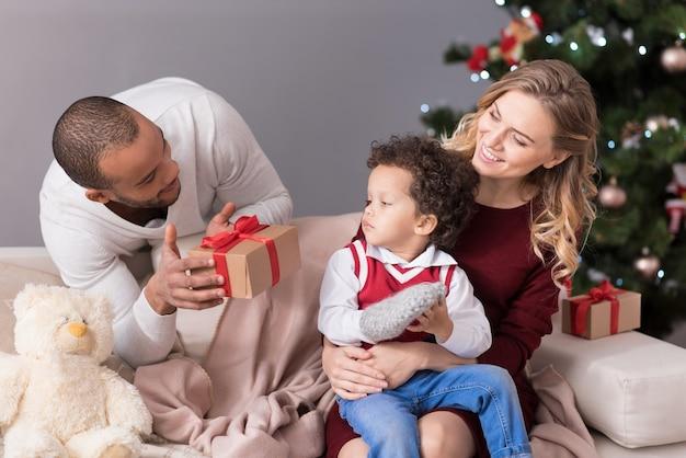 Geschenk an meinen sohn. hübscher, positiv entzückter mann, der hinter dem sofa steht und seinen sohn ansieht, während er eine geschenkbox für ihn hält