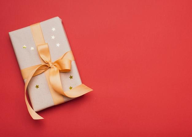 Geschenk bedeckt in den goldenen sternen mit kopienraum