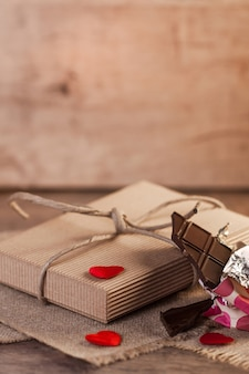 Geschenk der herzen, der schokolade und des valentinsgrußes auf hölzernem hintergrund
