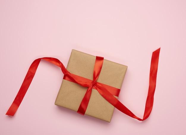 Geschenk eingewickelt in braunes kraftpapier auf einem rosa hintergrund