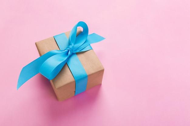 Geschenk eingewickelt und mit blauem bogen auf rosa hintergrund mit kopienraum verziert. flachgelegt, draufsicht