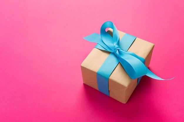 Geschenk eingewickelt und mit blauer schleife auf rosa verziert