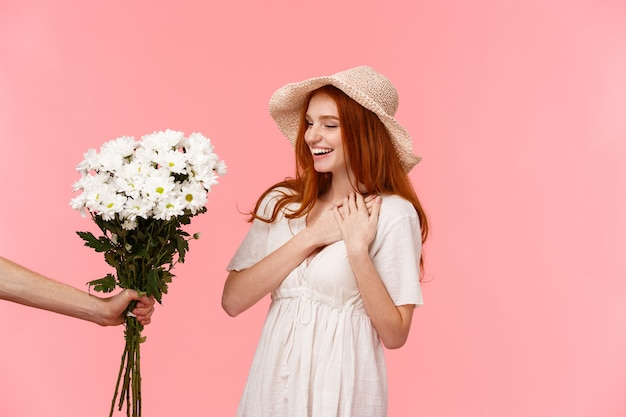 Geschenk-, feier- und weichheitskonzept. überraschte nette, anziehende rothaarigefrau im hut, kleid, bezaubert mit dem angenehmen geschenk, händchenhalten auf dem herzen schmeichelte und lächelte und betrachtete blumenstraußblumen