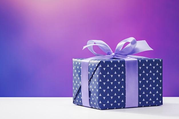 Geschenk für mann box in grauem papier mit blauem band lila oberfläche kopierraum