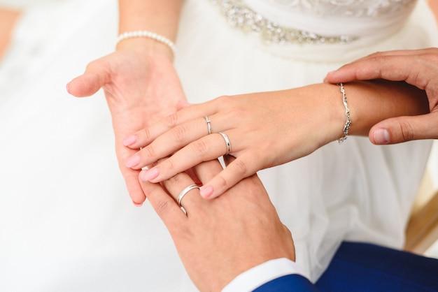 Geschenk für valentinsgrüße, verlobungs- und eheringe in den händen der braut und des bräutigams.