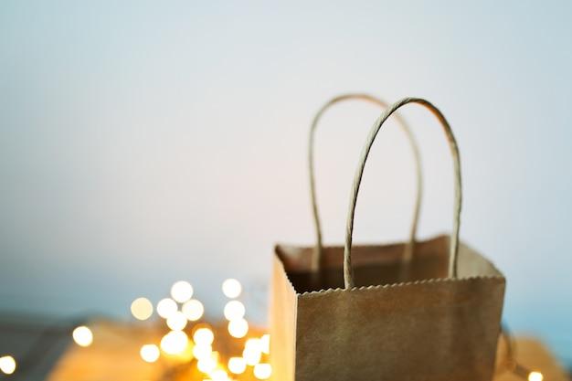 Geschenk handwerk paket steht vor dem hintergrund der weihnachtsgirlande und bokeh