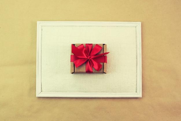 Geschenk im draufsicht-kopienraum des roten bogens des kraftpapierkastens