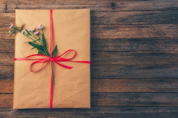 Geschenk im packpapier gebunden mit roter band- und gänseblümchenblume auf hölzernem retro-