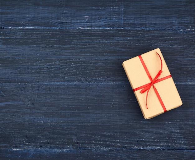 Geschenk in braunes kraftpapier eingewickelt und mit einem dünnen seidenband gebunden