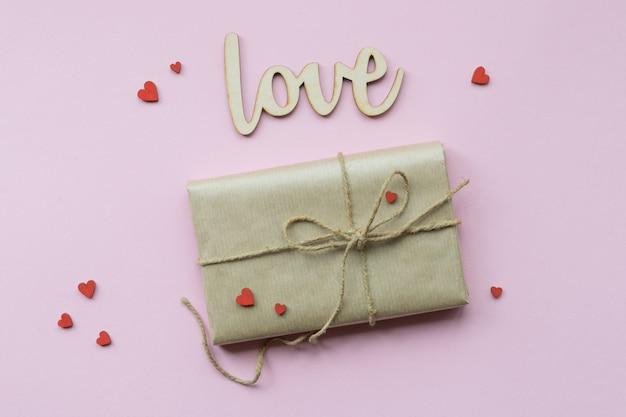 Geschenk in braunes kraftpapier gewickelt und hanfschnur gebunden. romantisches geschenk mit dekorativen roten herzen. ansicht von oben.