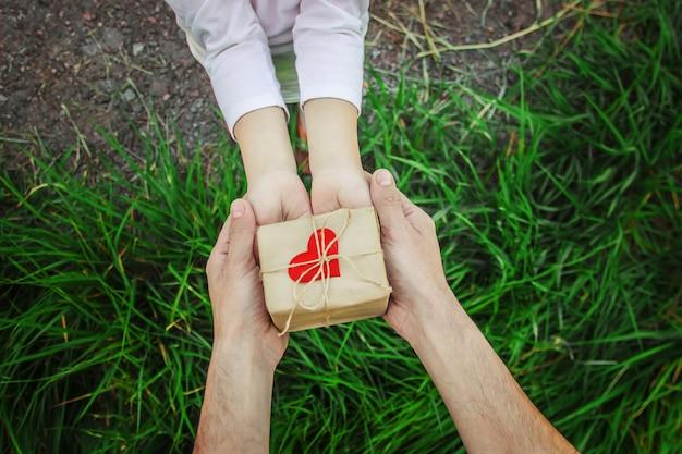 Geschenk in den händen eines kindes. glückwünsche zum tag seines vaters.