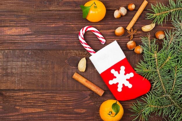 Geschenk in der weihnachtssocke, in der mandarine, in der süßigkeit, in den nüssen, im zimt auf dunklem holz