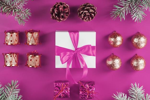 Geschenk in einer weißen schachtel und christbaumschmuck auf einer rosa wand. rosa konzept von weihnachtsdekorationen