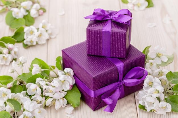 Geschenk in lila box für verschiedene feiertage. auf hölzernem hintergrund sind blühende zweige eines apfelbaums.