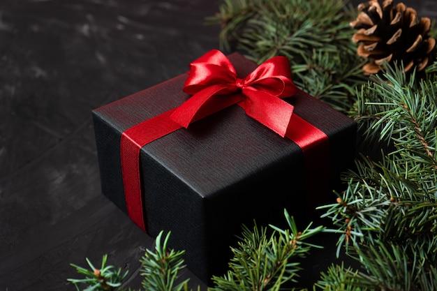 Geschenk in schwarz mit rotem band und schleife auf dunklem hintergrund mit tannenzweigen und zapfen