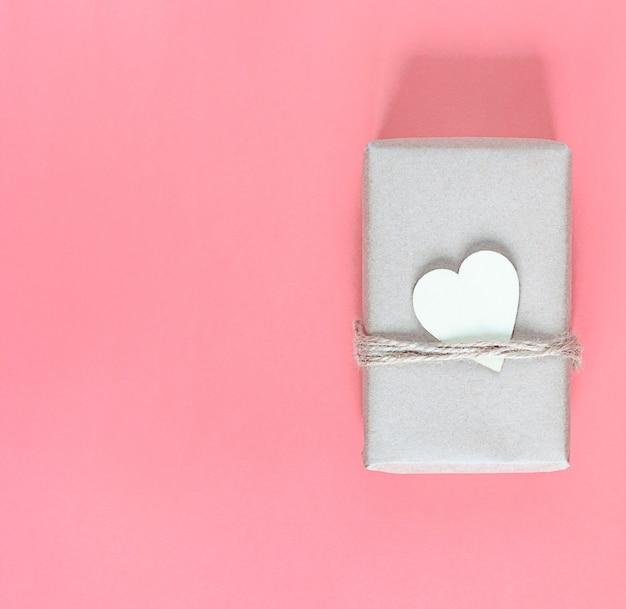 Geschenk in umweltfreundlicher handwerksverpackung und mit holzherz für den feiertag auf einem rosa hintergrund.