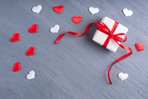 Geschenk in weißem papier mit rotem band, weißer und roter herzform auf stilvollem grauem schmutzhintergrund